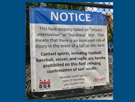 """Sign on artificial turf field stating that the field failed an """"impact attenuation"""" or """"hardness"""" test, which means that there is an increased risk of injury in the event of a fall."""